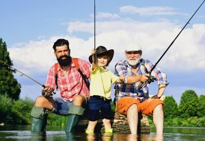 A young boy fishing with his dad and granddad.